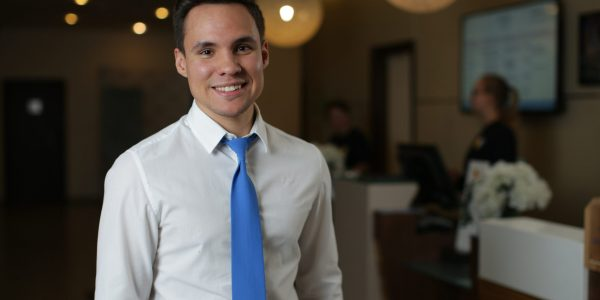 A young hotel administrator in a white shirt and blue tie stands against the front desk. Looks at the camera and smiles
